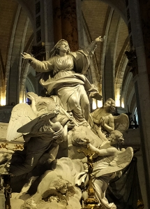 "The enormity and beauty of the sculpture at the high altar is compelling. It can be seen even from the back of this vast cathedral. ""The Assumption of Mary"" by Charles-Antoine Bridan bids visitors down the long central nave and rewards them with a beatific view of the Divine Feminine--arms flung wide, supported by the hosts of heaven."