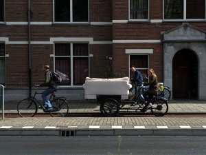 Bicycles are used for everything in Amsterdam. Here, a young lady transports a sofa on sort of a bike trailer.