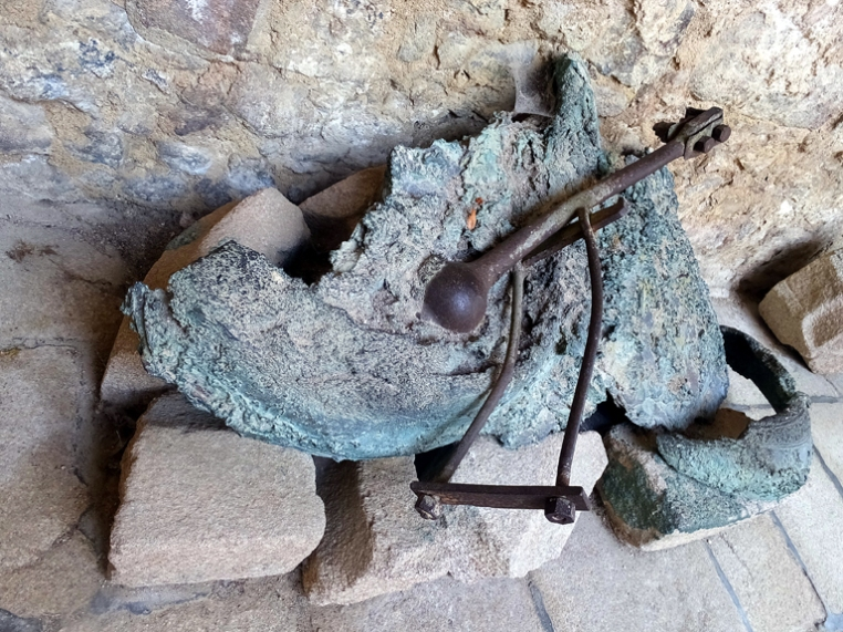 The church's bell, melted and deformed by the intense heat, gives mute testimony to the suffering of the victims.