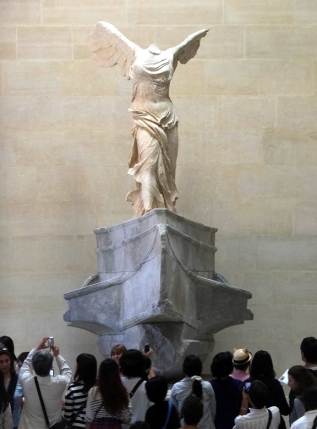 """Crowds can be horrible. Here the famous sculpture, the so-called """"Winged Victory,"""" would be lost in the crowd if it were not elevated."""