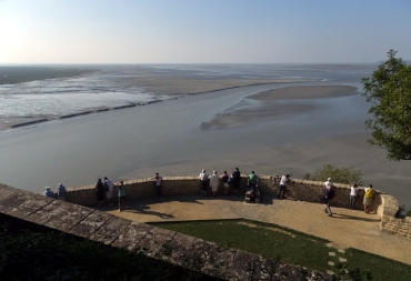"""It was low tide when we visited. At high tide Mont Saint-Michelis completely surrounded by water. A helicopter circles the area when the low tide starts to turn, looking for pilgrims making their way across the flat on foot. We were told that the tide comes in """"like a galloping horse."""""""