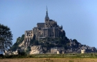 Visitors to Mont St. Michel see it first from miles away as a small mountain looming above some of the flattest terrain is France. This is a telephoto view from the visitors parking lot a mile-and-a-half from the island.