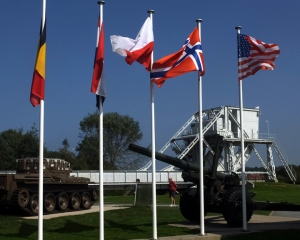 "Pegasus Bridge, site of the first casualties on D-Day. It is no longer in use but has been reassembled near the original site and restored as a memorial. The British squadron that captured and held this critical bridge had landed silently in three 30-man gliders and took the Nazis by surprise. After the war the bridge was renamed ""Pegasus"" because that was the insignia on their uniforms. The flags of every nation that participated in the D-Day invasion are flown."