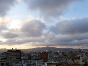 The ever-changing sky over the distant mountains offered a serene contrast to the teeming life of the city.