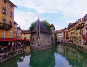 Annecy is located on Lake Annecy, near Geneva, Switzerland. It is bisected by the Thiou River. In the middle of the river, the Palais d'Isle was originally the home of the Lord of Annecy. Since then it has served as a courthouse, a mint, and a prison.