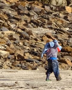 I spotted this boy playing with his family along the rocky coastline. His dirty and disheveled clothing reflects the good time he was having!