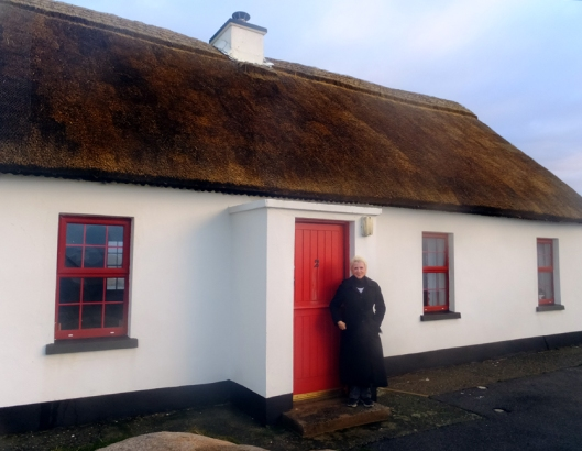 Here Sarah stands in front of the thatched-roofed cottage where she and her friend Margaret stayed in 1996.