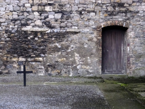 A small cross stands on the spot where the men stood before the firing squads, beside the door through which their dead bodies would be carried.